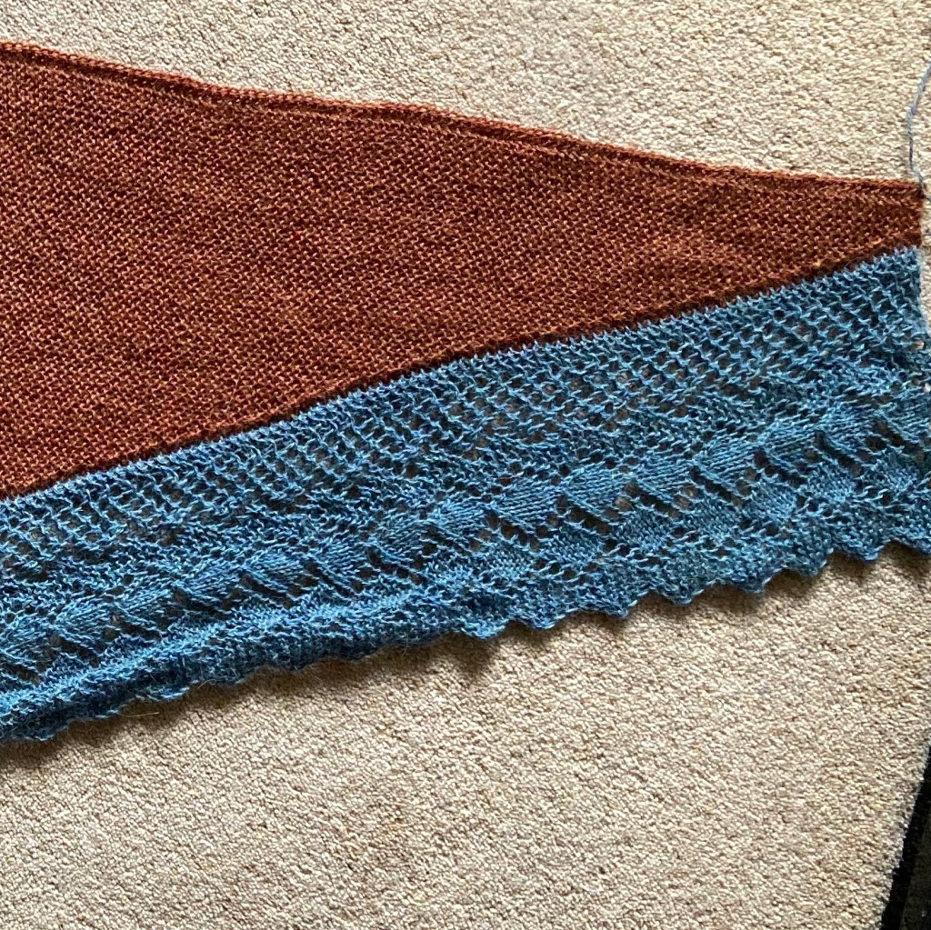 A copper coloured garter stitch shawl with a silvery deep edging lies on a pale carpet. Part of the edging has been blocked and lies flat, the rest is bunched up.
