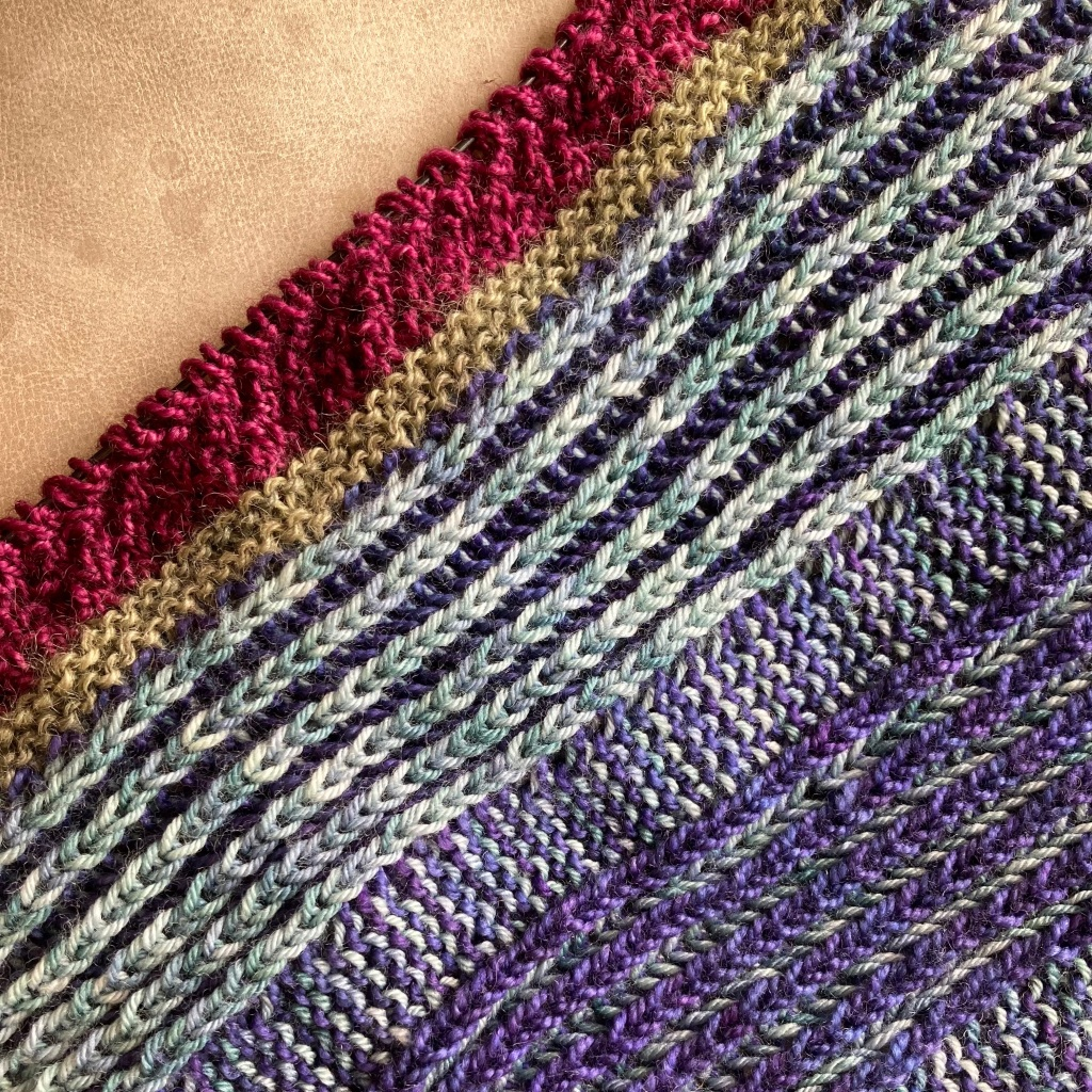 A close-up photo of Brioche +Mystery in progress. Dark purple and light blue fill most of the image, with olive green and magenta stripes outside it.