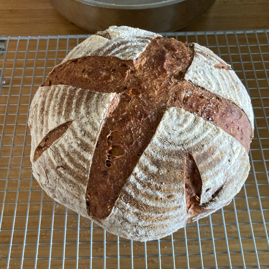 A seeded sourdough loaf with a cross scored across the floured top sits on a metal cooling rack.