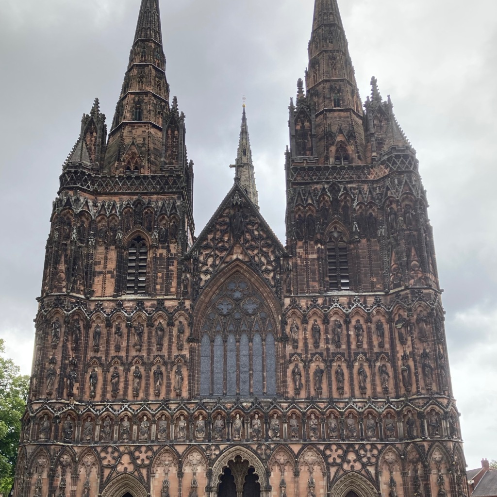The frontage of Lichfield Cathedral with a cloudy grey sky behind. The building is covered in sculptures of kings, queens, angles and saints with lots of geometric details.