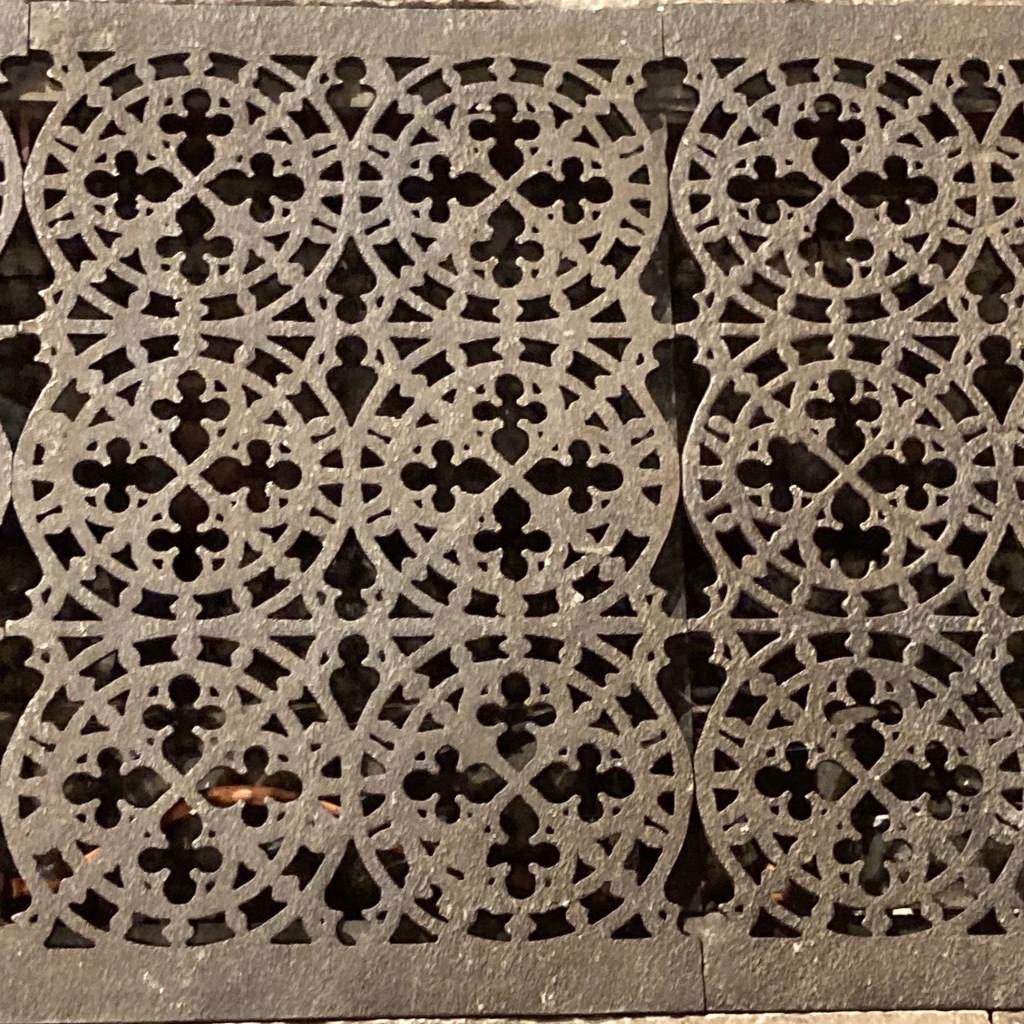 A close up of a cast iron floor grating. Each piece is two circles wide and three high with diamonds running through the circles and decorative points like the tops of church windows all through the design.
