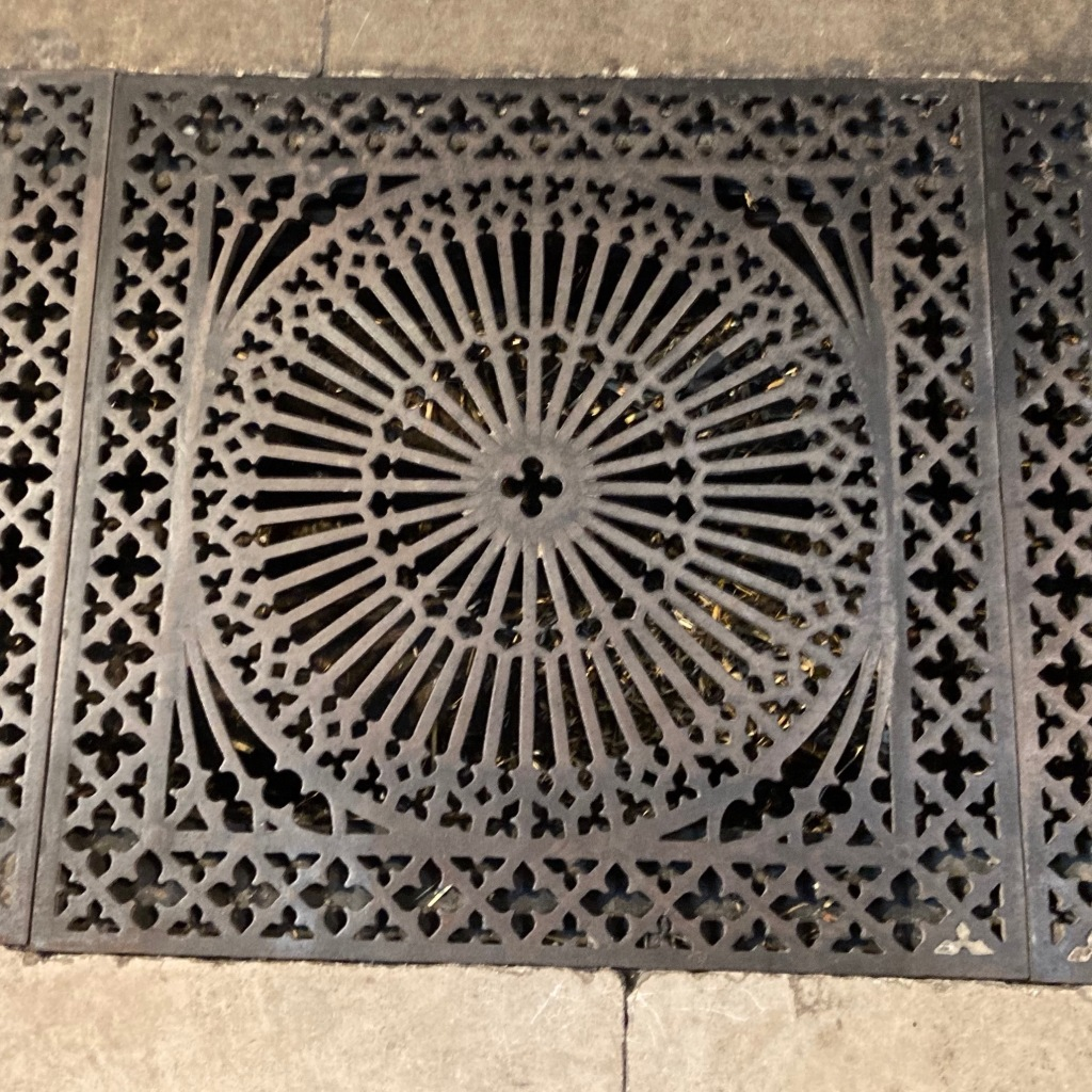 A square cast iron floor grating with a large circle surrounded with a border of diamonds. The circle has 'spokes' spreading from the centre, with the detail near the edge of the circle taking the form almost of fleurs de lyes, similar to the tops of church windows.