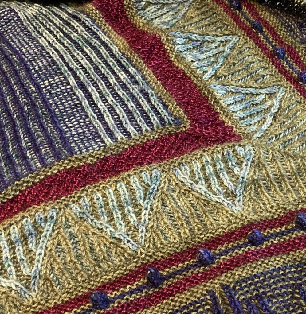 A close up of part of a brioche knitted shawl in four colours. There are two colour brioche stripes surrounded on two sides by textural stripes, then triangle shapes in two-colour brioche, followed by garter stitch stripes in three colours with bobbles in the centre stripe.