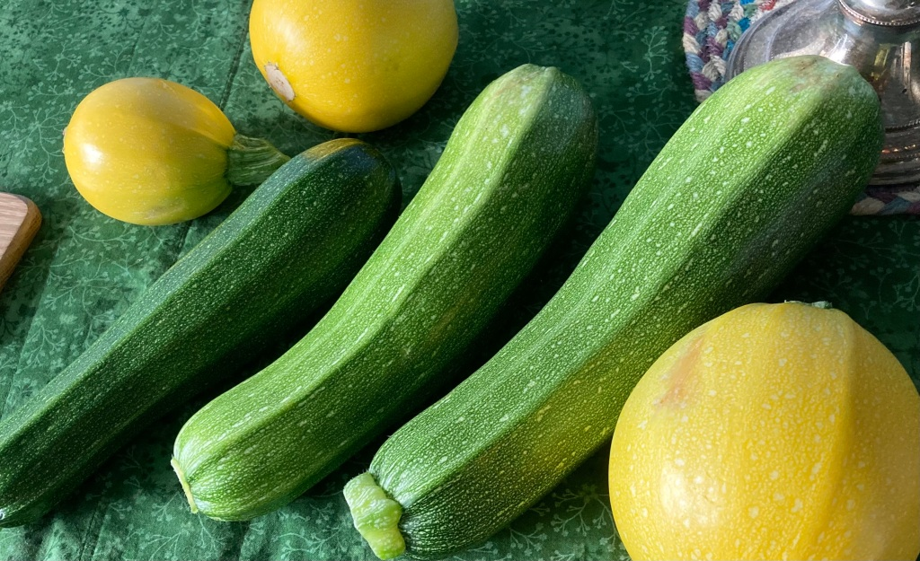 Three large green courgettes lie on a green tablecloth with three round yellow courgettes of various sizes. In the top left corner is a woven placemat with the base of a silver candlestick just showing.