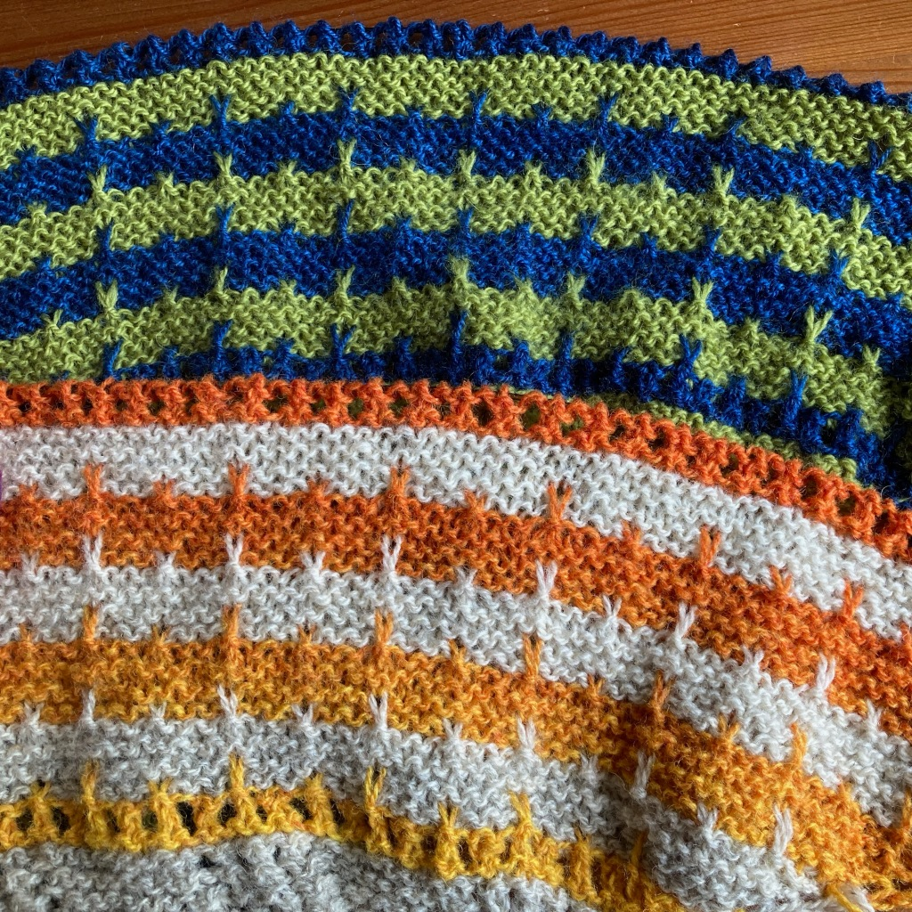 Two lots of striped slipped stitch knitting laid on top each other. The bottom half of the image is a light neutral striped with bright yellow that changes to orange by mid-screen. The top half of the image is the same pattern in solid dark blue striped with an olive green.