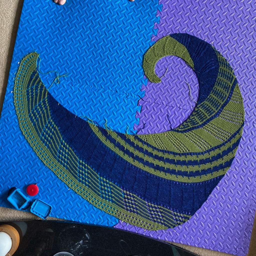 A dark blue and olive green vortex shawl is pinned out on large blue and purple play mats. The shawl is in blocks of solid colours and stripes, using slip stitch patterns and lace. The black marble of the hearth is at the bottom of the image.