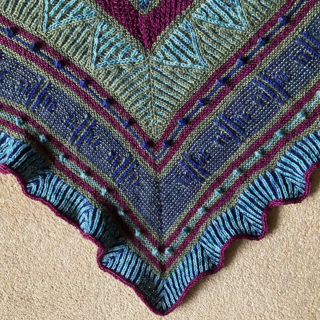 A close-up of a shawl worked in a mixture of garter stitch, two colour brioche, bobbles and an i-cord edging. The four yarn colours are combined in different ways to create a variety of effects.