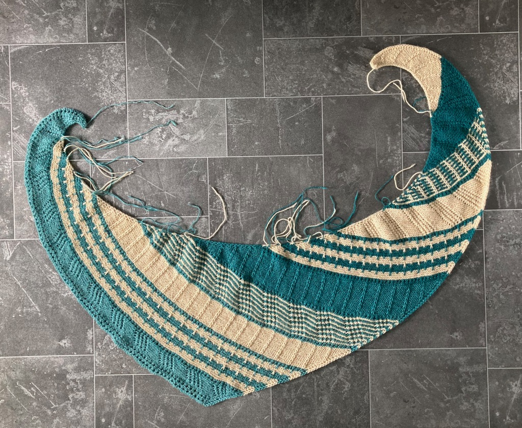 A vortex shaped shawl in a light sand and shades of teal lies on a dark grey floor. The shawl uses garter stitch, slip stitch patterns and lace.