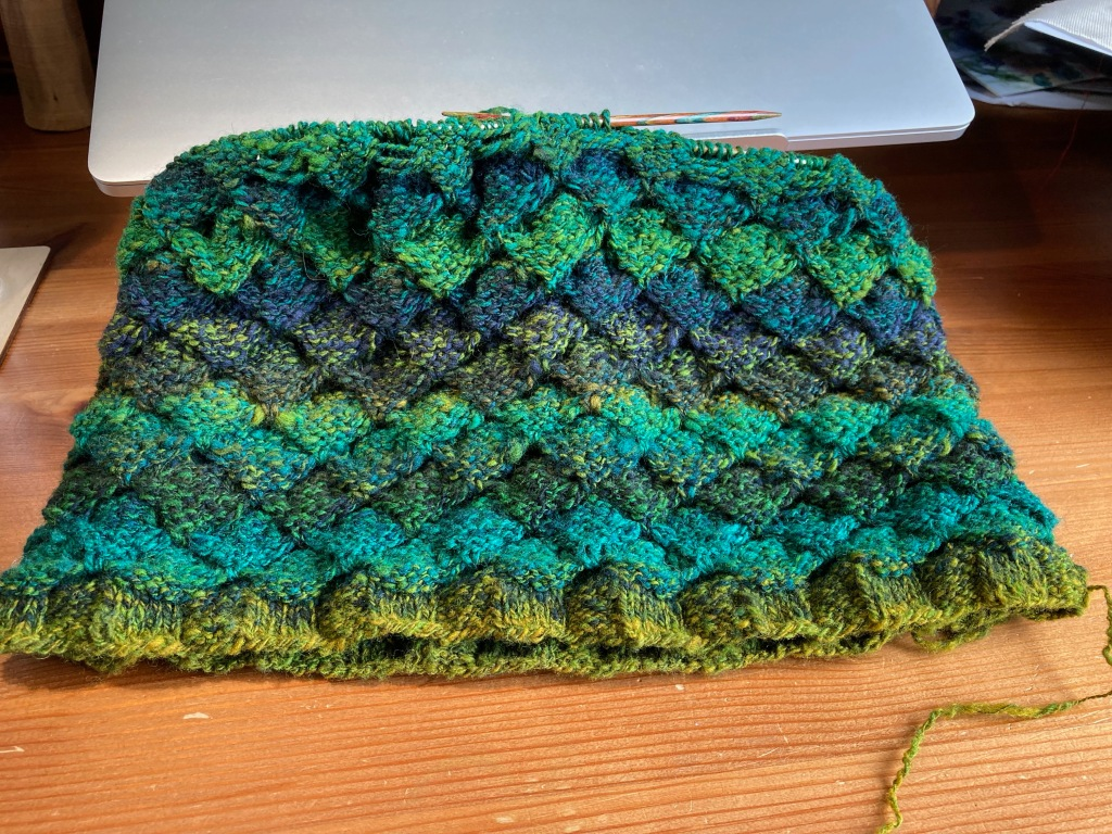 A textural knitted cowl in progress lies on a wooden desk against a closed laptop. It is in shades of blue, green and grey-gold with a tucked slip stitch pattern. The yarn is hand-spun.