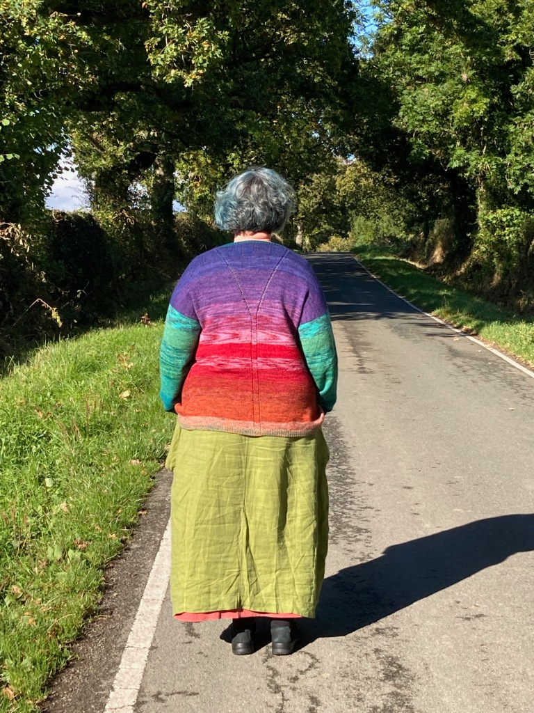 A woman wearing a hand-knit sweater and a linen dress stands with her back to the camera and her hands in her pockets in a country lane. It is a sunny day and the jewel colours of the sweater almost glow.