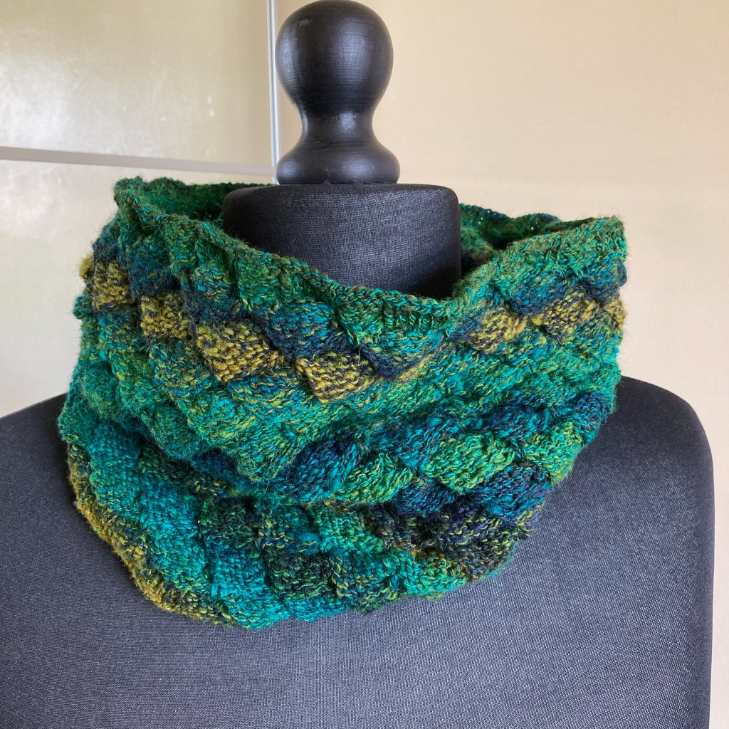 A hand-knit cowl in hand-spun shades of blue, green and greeny-gold wool is on a mannequin covered with black fabric. A cream wall is reflected in the mirrored door behind.