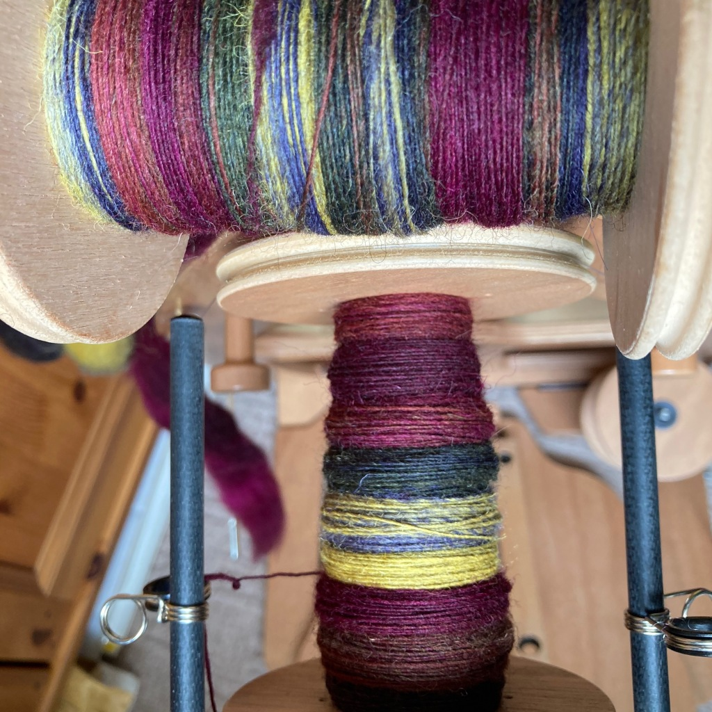 A close-up of a bobbin in progress on the spinning wheel, with the other bobbin balanced horizontally above it to show the contrast. The wheel treadles and rest of the background are out of focus.