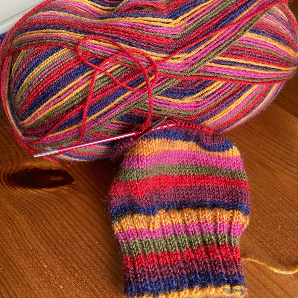 A brightly coloured stripy sock in progress sits on a wooden desk in front of its ball of yarn. The yarn is pink, yellow, dark blue, maroon, scarlet and olive green.